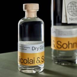 Nicolai & Sohn Dry Gin. Produkt der Brennerei auf einem grünem Tisch vor schwarzer Wand. The Classic Edition